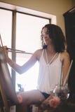 Το κορίτσι καλλιτεχνών χρωματίζει την εικόνα στον καμβά στο στούντιο στοκ φωτογραφία με δικαίωμα ελεύθερης χρήσης