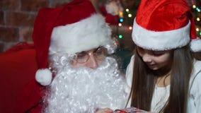 Το κορίτσι κινηματογραφήσεων σε πρώτο πλάνο λαμβάνει ένα δώρο από Άγιο Βασίλη φιλμ μικρού μήκους