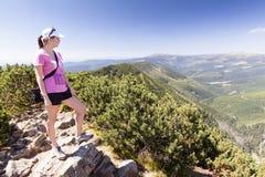 Το κορίτσι κοιτάζει έξω πέρα από τα βουνά, πεζοπορώ Στοκ Εικόνες