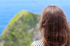 Το κορίτσι κοιτάζει από τα βουνά στο ακρωτήριο και τον ωκεανό στοκ φωτογραφία με δικαίωμα ελεύθερης χρήσης