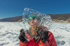 Το κορίτσι κοιτάζει μέσω ενός διαφανούς επιπλέοντος πάγου πάγου στη λίμνη baikal Στοκ Εικόνες