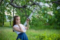 Το κορίτσι κοιτάζει μέσω των δάχτυλών της κάτω από το δέντρο μηλιάς στοκ εικόνες με δικαίωμα ελεύθερης χρήσης