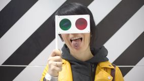 Το κορίτσι κοιτάζει στα γυαλιά με τα χρωματισμένα γυαλιά, παίζει με τους απόθεμα βίντεο