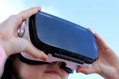 Το κορίτσι κοιτάζει στα γυαλιά της εικονικής πραγματικότητας του άσπρου χρώματος στοκ φωτογραφίες
