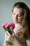 Το κορίτσι κοιτάζει στα λουλούδια Στοκ Φωτογραφία
