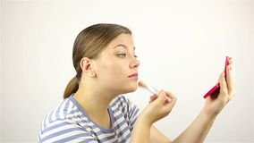 Το κορίτσι κοιτάζει στον καθρέφτη και κονιοποιεί το πρόσωπό της φιλμ μικρού μήκους