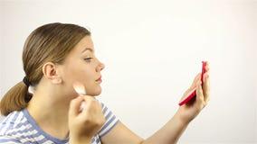 Το κορίτσι κοιτάζει στον καθρέφτη και κονιοποιεί το πρόσωπό της απόθεμα βίντεο