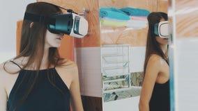 Το κορίτσι κοιτάζει στον καθρέφτη στο λουτρό με τα γυαλιά εικονικής πραγματικότητας στο κεφάλι συσκευή φιλμ μικρού μήκους