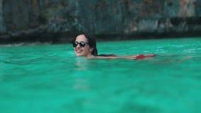 Το κορίτσι κολυμπά και χαμογελά στο τυρκουάζ νερό φιλμ μικρού μήκους