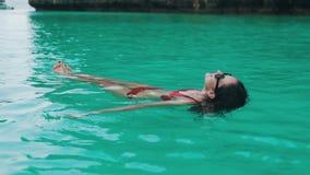 Το κορίτσι κολυμπά στην τυρκουάζ κινηματογράφηση σε πρώτο πλάνο νερού φιλμ μικρού μήκους