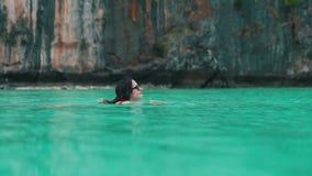 Το κορίτσι κολυμπά στο νερό του τυρκουάζ ωκεανού φιλμ μικρού μήκους