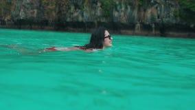 Το κορίτσι κολυμπά στο τυρκουάζ νερό απόθεμα βίντεο