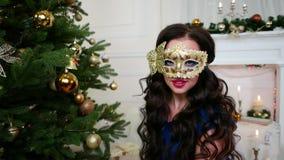 Το κορίτσι κομμάτων του νέου έτους στη μάσκα μεταμφιέσεων, γιορτάζει τα Χριστούγεννα κοντά στο χριστουγεννιάτικο δέντρο, εξετάζον φιλμ μικρού μήκους
