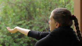 Το κορίτσι κολλά το χέρι της κάτω από τη βροχή, που προσπαθεί να συλλέξει τις μειωμένες σταγόνες βροχής απόθεμα βίντεο