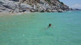 Το κορίτσι κολυμπά στον ήρεμο κυανό ωκεανό κοντά στη δύσκολη παραλία απόθεμα βίντεο