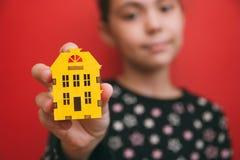 Το κορίτσι κρατά ένα μικρό κίτρινο εγχώριο εικονίδιο σε ένα κόκκινο υπόβαθρο και μια εστίαση στην οικοδόμηση του ρηχού βάθους στοκ εικόνες