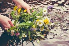 Το κορίτσι κρατά ένα στεφάνι των λουλουδιών επάνω από το νερό στοκ εικόνες με δικαίωμα ελεύθερης χρήσης
