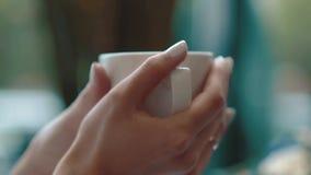 Το κορίτσι κρατά ένα φλιτζάνι του καφέ με τα χέρια της ενώ σε έναν καφέ, κινηματογράφηση σε πρώτο πλάνο φιλμ μικρού μήκους
