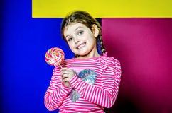 Το κορίτσι κρατά μια μεγάλη πολύχρωμη καραμέλα στοκ φωτογραφίες
