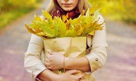 Το κορίτσι κρατά μια συσκευασία με τα φύλλα Στοκ Φωτογραφία