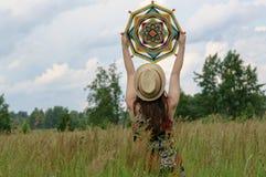 Το κορίτσι κρατά πέρα από το κεφάλι ενός mandala Στοκ φωτογραφίες με δικαίωμα ελεύθερης χρήσης