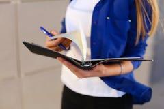 Το κορίτσι κρατά στο ημερολόγιο χεριών, το σημειωματάριο με τα φύλλα και τη μάνδρα και το φύλλο Στοκ εικόνα με δικαίωμα ελεύθερης χρήσης