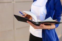 Το κορίτσι κρατά στο ημερολόγιο χεριών, το σημειωματάριο με τα φύλλα και τη μάνδρα και το φύλλο Στοκ Φωτογραφίες