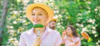 Το κορίτσι κρατά τα δίκρανα με το λουκάνικο και το αγγούρι Εναλλακτική διατροφή για τους χορτοφάγους Ο χορτοφάγος τρόπος ζωής είν στοκ φωτογραφία