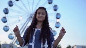 Το κορίτσι κρατά τα πυροτεχνήματα στα χέρια της και χαίρεται τη στάση στο υπόβαθρο της ρόδας ferris κίνηση αργή απόθεμα βίντεο