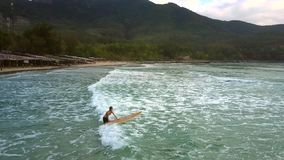 Το κορίτσι κρατά την ιστιοσανίδα στο νερό περπατώντας στα foamy κύματα απόθεμα βίντεο
