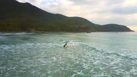 Το κορίτσι κρατά την ιστιοσανίδα στο νερό υπερνικώντας τα foamy κύματα απόθεμα βίντεο