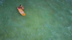 Το κορίτσι κρατά την ιστιοσανίδα υπερνικώντας το foamy ωκεάνιο κύμα απόθεμα βίντεο