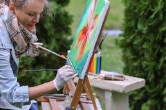 Το κορίτσι κρατά τη βούρτσα και είναι υπογεγραμμένη ζωγραφική, στεμένος στο outdoo πάρκων Στοκ Φωτογραφίες
