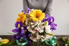 Το κορίτσι κρεμά την ανθοδέσμη στα χέρια Εστίαση στα λουλούδια Στοκ Εικόνες