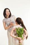 Το κορίτσι κρύβει μια ανθοδέσμη των λουλουδιών για τη μητέρα Στοκ Εικόνα