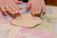 Το κορίτσι κυλά τη ζύμη Προετοιμάζοντας τις ζύμες στο σπίτι στην κουζίνα στοκ φωτογραφία με δικαίωμα ελεύθερης χρήσης