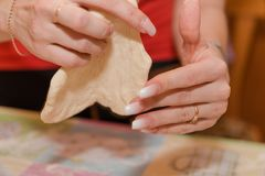 Το κορίτσι κυλά τη ζύμη Προετοιμάζοντας τις ζύμες στο σπίτι στην κουζίνα στοκ εικόνα