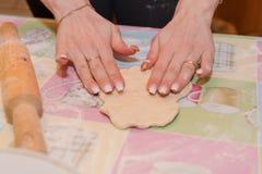 Το κορίτσι κυλά τη ζύμη Προετοιμάζοντας τις ζύμες στο σπίτι στην κουζίνα στοκ εικόνες με δικαίωμα ελεύθερης χρήσης