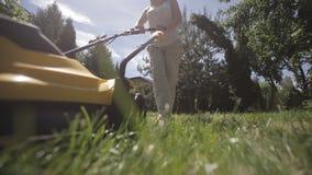 Το κορίτσι κόβει έναν ανώμαλο χορτοτάπητα με τον κίτρινο χορτοκόπτη ξυπόλυτο φιλμ μικρού μήκους