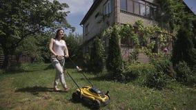 Το κορίτσι κόβει έναν ανώμαλο χορτοτάπητα με τον κίτρινο χορτοκόπτη ξυπόλυτο απόθεμα βίντεο