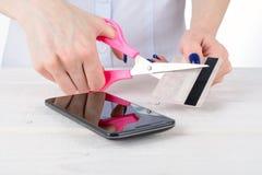 Το κορίτσι κόβει μια πιστωτική κάρτα πέρα από το τηλέφωνο Στοκ εικόνα με δικαίωμα ελεύθερης χρήσης
