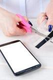 Το κορίτσι κόβει μια πιστωτική κάρτα πέρα από το τηλέφωνο Στοκ Εικόνα