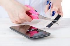 Το κορίτσι κόβει μια πλαστική κάρτα πέρα από το τηλέφωνο Στοκ Εικόνες