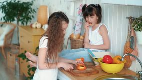 Το κορίτσι κόβει το πιπέρι στην κουζίνα, η αδελφή της κάθεται στον πίνακα και τρώει το κουλούρι, σε αργή κίνηση φιλμ μικρού μήκους