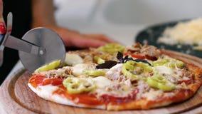 Το κορίτσι κόβει την πίτσα στην κουζίνα απόθεμα βίντεο