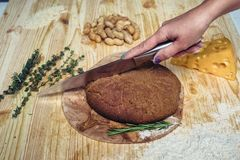 Το κορίτσι κόβει το φρέσκο ψωμί από το αλεύρι αμάραντων πρόγευμα υγιές Στοκ Εικόνες