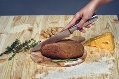 Το κορίτσι κόβει το φρέσκο ψωμί από το αλεύρι αμάραντων πρόγευμα υγιές Στοκ Εικόνα