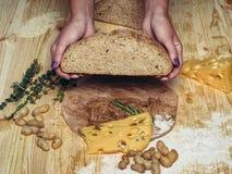 Το κορίτσι κόβει το φρέσκο ψωμί από το αλεύρι αμάραντων πρόγευμα υγιές Στοκ Φωτογραφία