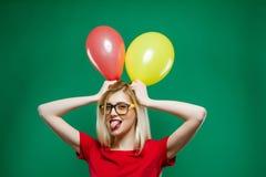 Το κορίτσι κόμματος στα μοντέρνα γυαλιά μορφάζει και εξετάζει τα κίτρινα και κόκκινα μπαλόνια αέρα εκμετάλλευσης καμερών Στοκ Εικόνα