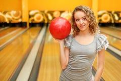 το κορίτσι λεσχών μπόουλινγκ σφαιρών κρατά τις κόκκινες νεολαίες Στοκ Εικόνα